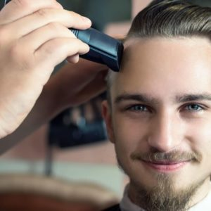 young man with blue eyes getting buzz cut